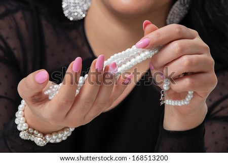 Beads pearls. Beautiful woman hands  with pink manicure holding white pearl necklace.. Pearls and Nails concept - stock photo