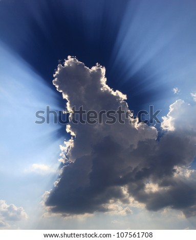 Beam of light behind the clouds - stock photo