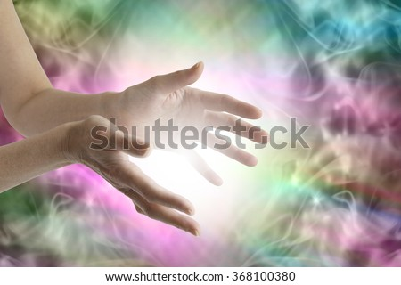 Beaming healing energy - Outstretched female healing hands with white light between and a vibrant multicolored flowing energy field background - stock photo