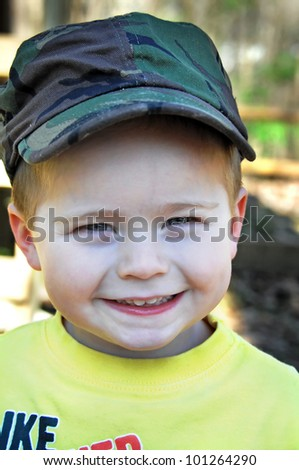 Beaming little boy is wearing a smile from ear to ear and a camouflaged hat. - stock photo