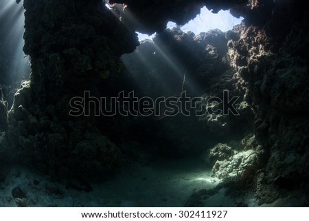 Beams of light descend into the shadows of a dim cavern in the Solomon Islands. Coral reefs in this Melanesian region are exceedingly diverse. The area also offers great scuba diving and snorkeling.