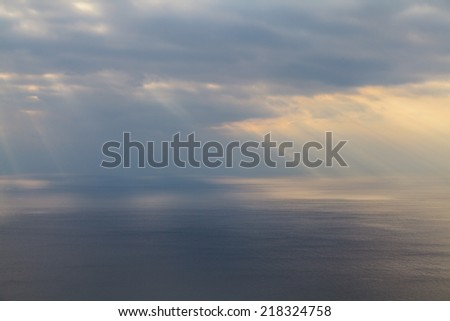 Beams of the sun make the way through clouds and fall on the sea. - stock photo