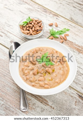 Bean soup in a plate on wooden table