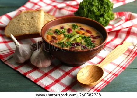Bean soup in bowl with fresh sliced bread on napkin, on wooden table background - stock photo
