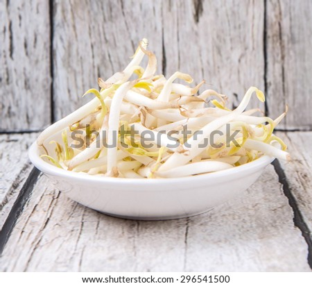 Bean sprout in white bowl over weathered wooden background - stock photo