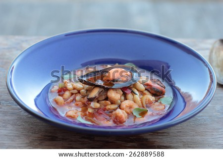 Beans and chorizo cooked with seafood on a blue plate. - stock photo