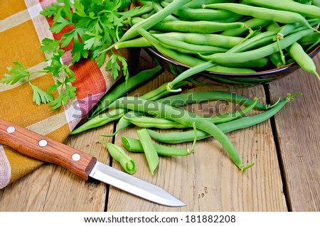Beans asparagus green, checkered napkin, knife, parsley on a wooden boards background - stock photo