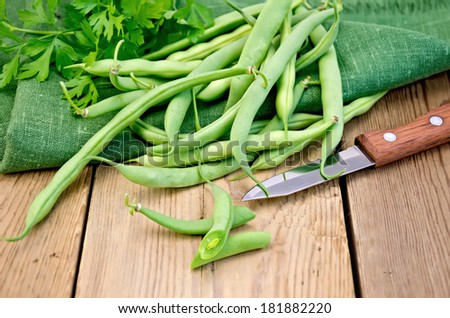 Beans asparagus green, green napkin, knife, parsley on a wooden boards background - stock photo
