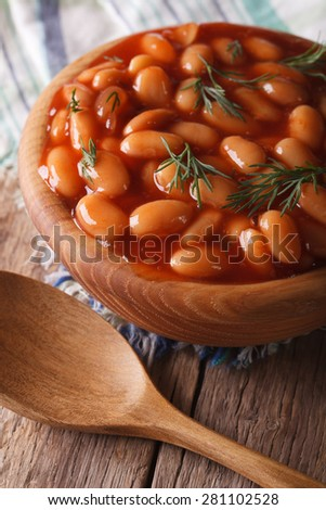beans in tomato sauce in a wooden bowl closeup. Vertical - stock photo