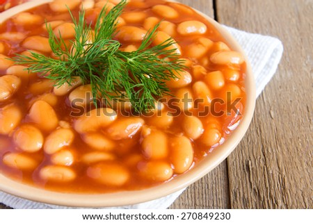 Beans in tomato sauce with dill on wooden background, close up horizontal - stock photo