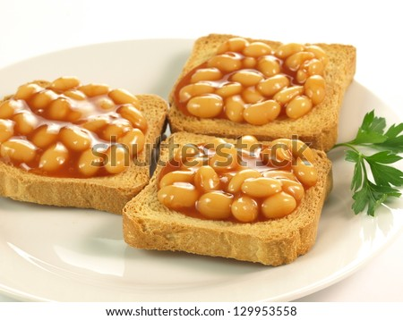 Beans on toast on plate on isolated background - stock photo