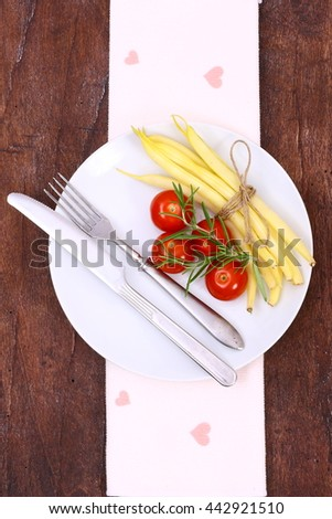 Beans, tomatoes and fresh herbs on a wooden table. Healthy vegetables background. - stock photo