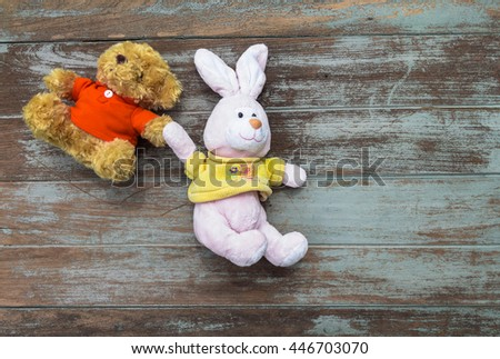 Bear and Rabbit doll hold each another hand, help and friend concept - stock photo