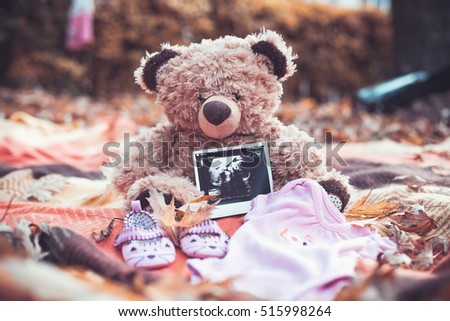 Bear cub with a photo of the child and children's clothes