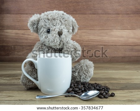 Bear doll, white cup, silver spoon and coffee beans on wooden table.