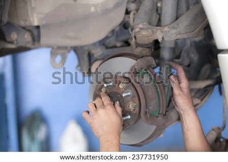 bear hands fixing car wheel hub, disc brake - stock photo