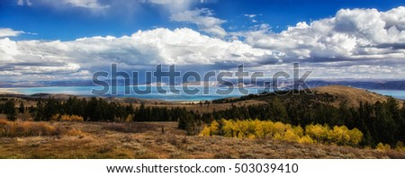 Bear Lake in the distance with storm clouds rolling past and golden aspens on the hillside below in Utah USA.
