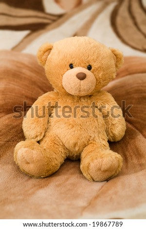 bear toy sinning on the brown carpet - stock photo