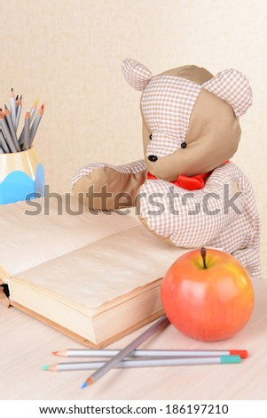 Bear toy with book on light background - stock photo
