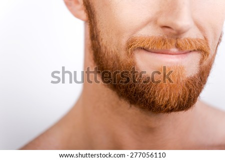 Beard is his style. Close-up of bearded man smiling while standing against white background - stock photo