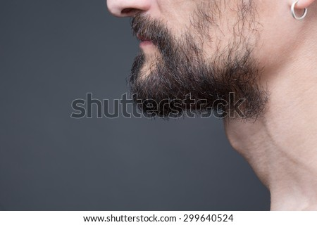 Beard is his style. Close-up profile of bearded man standing against dark grey background without any emotions, just calm. - stock photo