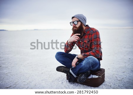 beard lumbersexual hipster sitting on suitcase in deep thought - stock photo