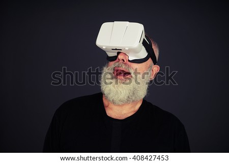 Beard senior man looking up surprised using virtual reality glasses, on black background