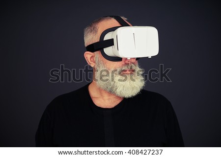 Beard senior man wearing hi-tech VR headset, on black background