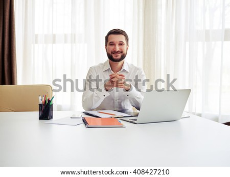 Beard smiling man sitting at the big white table and crossed his fingers in the modern white office