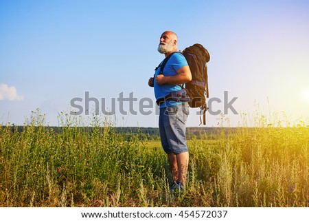Bearded aged man in good physical shape is standing in the grass carrying a rucksack and looking into the distance