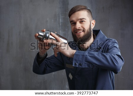 Bearded barman with shaker on a background of gray scratched concrete wall.
