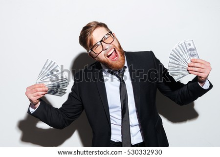 Bearded Business man in glasses and black suit with money in hands. Isolated gray background
