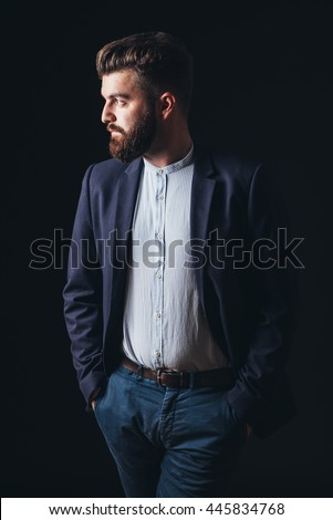 bearded businessman in a studio, isolated black, suit