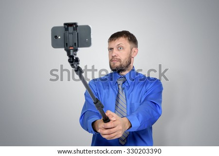 Bearded Businessman making selfie with a stick - stock photo