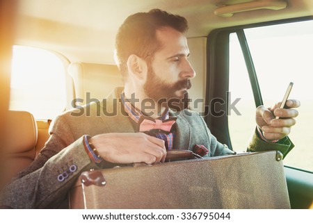 bearded businessman sitting on back seat of car with suitcase and touching phone with app - stock photo