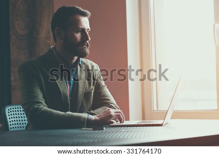 bearded businessman sitting with laptop and working - stock photo