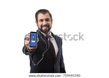 Bearded businessman with earphones showing smartphone with facebook website, isolated on white
