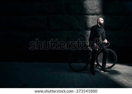 bearded caucasian bald man sits on black fix bicycle against black wall of stone. He sits in thin stripe of light. Street is empty. Man is wearing black shirt and trousers and sneakers.  - stock photo