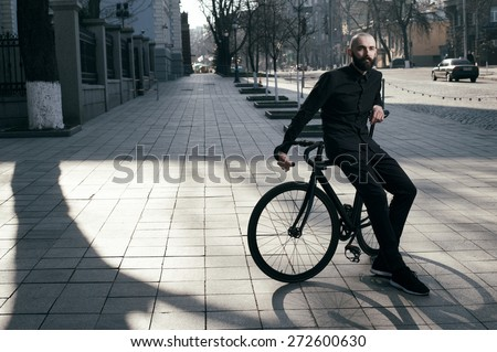 bearded caucasian bald man sits on black fix bicycle against cobbled street . He sits in morning light. There are silhouettes of people. Man is wearing black shirt and trousers and sneakers.  - stock photo
