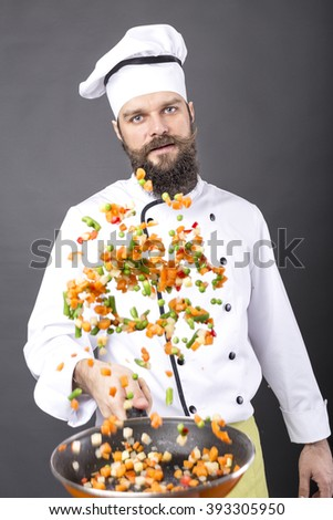 Bearded chef flipping vegetables in a frying pan over gray background