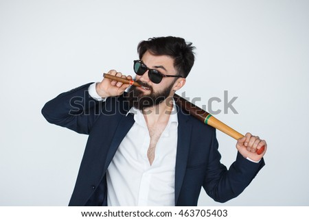 Bearded collector man with serious face, sunglasses, black suit, cigar and baseball bat isolated on white background