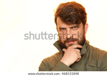 Bearded guy in khaki jacket holding his chin. Close.up. White