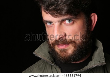 Bearded guy in khaki jacket with interesting look. Close.up. Black