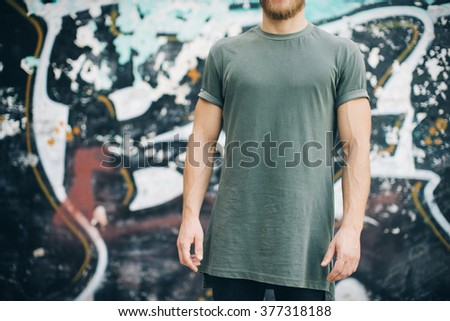 Bearded guy wearing green blank t-shirt and black jeans, standing on the street. horizontal - stock photo