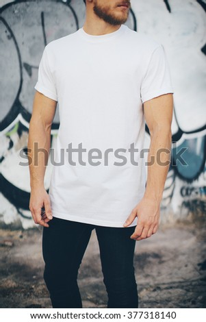 Bearded guy wearing white blank t-shirt and black jeans, standing opposite garage. Vertical - stock photo