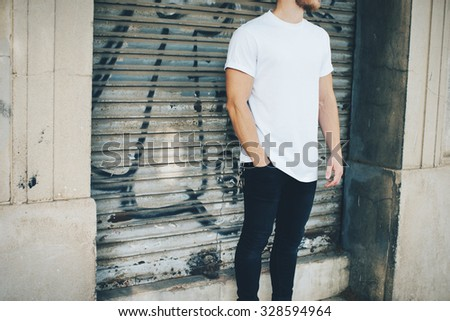 Bearded guy wearing white blank t-shirt and blue jeans, standing on the street - stock photo