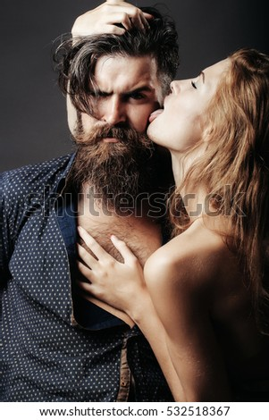 bearded handsome man and female slim flexible body of young pretty sexy woman or girl with bare back has long blonde hair licking male face