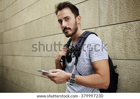 Bearded handsome man holding mobile phone while standing against street wall background with copy space, male traveler awaiting answer on his message on cell telephone during break between walking - stock photo