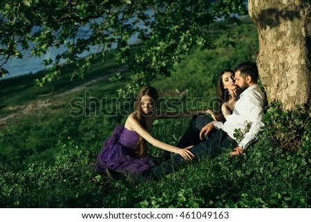 Bearded handsome man in white shirt smoking cigarette sitting with two young pretty women in violet dresses near tree on green grass sunny day outdoor