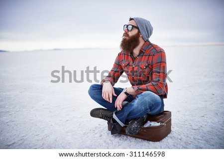 bearded hipster alone in the salt flats looking out in deep thought with copyspace composition - stock photo